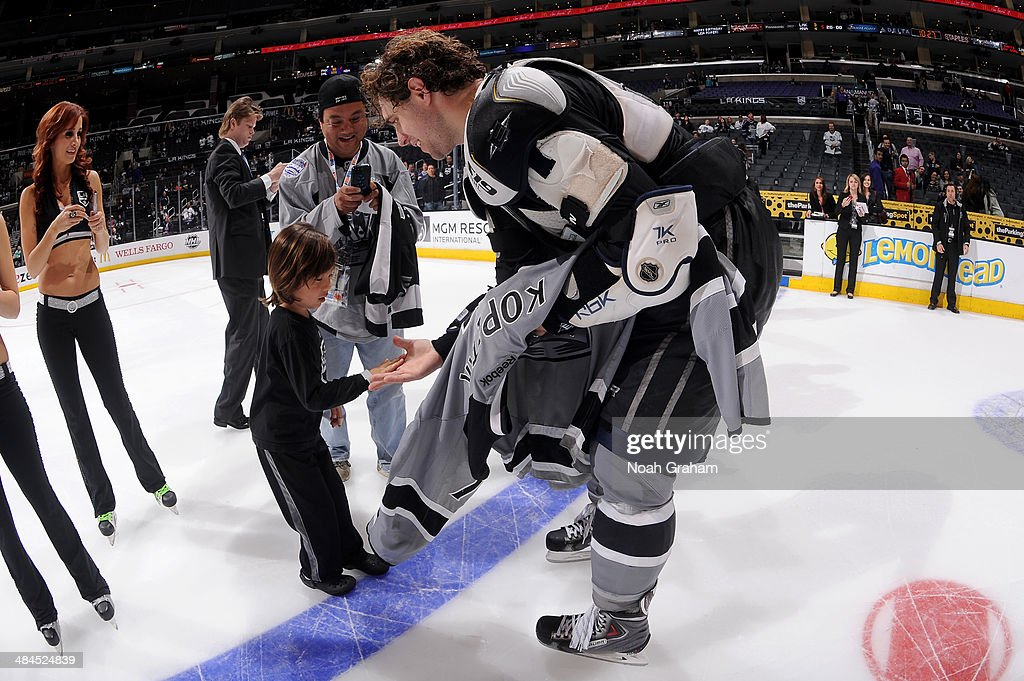 Anze Kopitar #11 of the Los Angeles Kings gives his jersey to a fan after the game against the Anaheim Ducks at Staples Center on April 12, 2014 in Los Angeles, California.