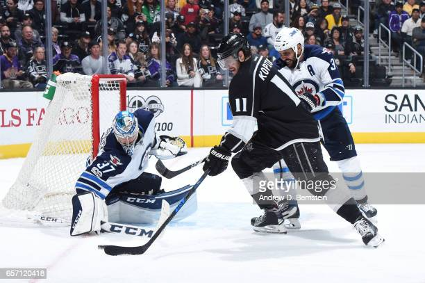 Anze Kopitar of the Los Angeles Kings handles the puck against Connor Hellebuyck and Dustin Byfuglien of the Winnipeg Jets at STAPLES Center on March...