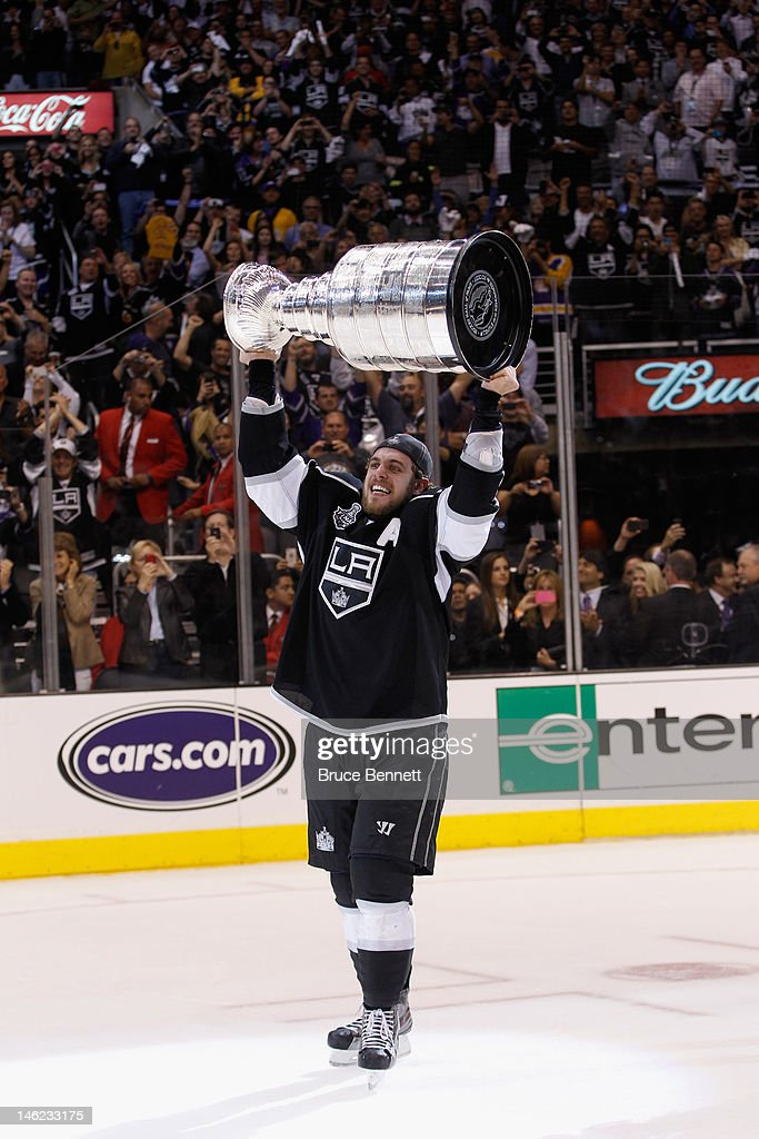 Anze Kopitar of the Los Angeles Kings holds up the Stanley Cup after the Kings defeated the New Jersey Devils 61 to win the Stanley Cup series 42 in...