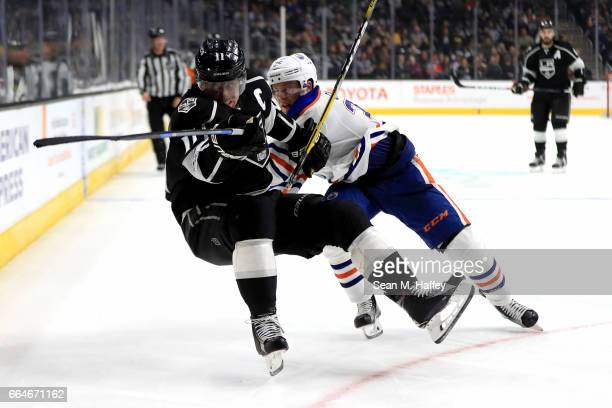 Anze Kopitar of the Los Angeles Kings is checked by Drake Caggiula of the Edmonton Oilers during the second period of a game at Staples Center on...