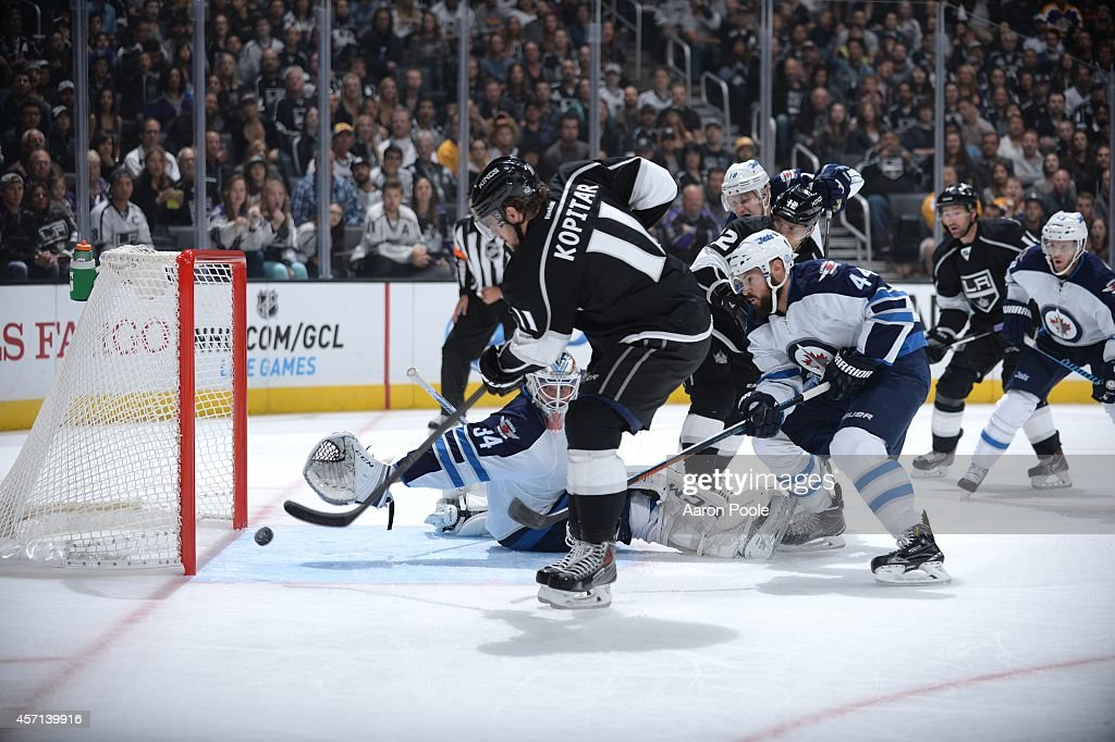 Anze Kopitar #11 of the Los Angeles Kings scores against Michael Hutchinson #34 of the Winnipeg Jets at STAPLES Center on September 12, 2014 in Los Angeles, California.