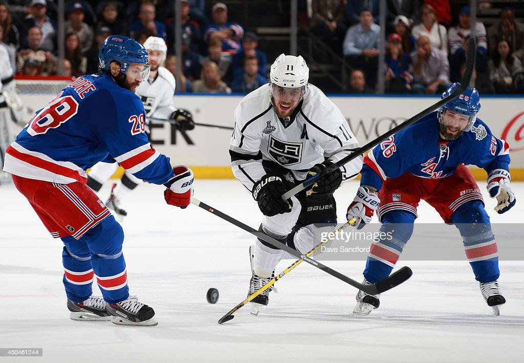 Anze Kopitar of the Los Angeles Kings tries to get past Dominic Moore and Martin St Louis of the New York Rangers in the second period of Game Four...