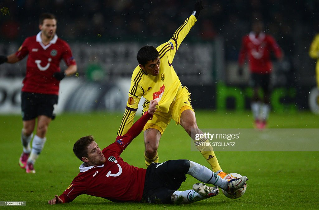Anzhi Makhachkala's Uzbek midfielder Odil Ahmedov (C) vies for the ball with Hanover's Belgian defender Sebastien Pocognoli (on the pitch) during the UEFA Europa League Round of 32 football match Hannover 96 vs FC Anzhi Makhachkala in Hanover, northern Germany on February 21, 2013.