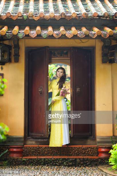 Ao Dai in Yellow stand at Pagoda Door