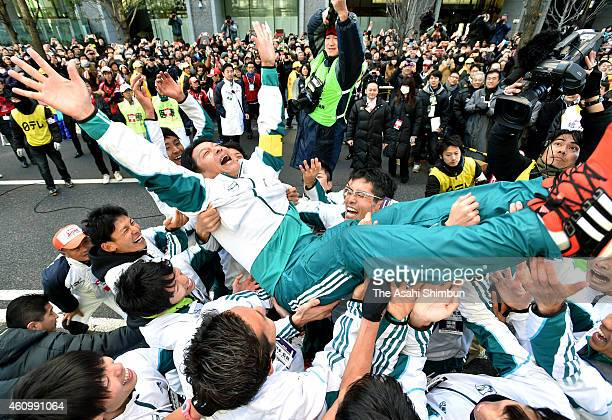 Aoyama Gakuin University head coach Susumu Hara is thrown into the air by his runners to celebrate winning in the 91st Hakone Ekiden on January 3...