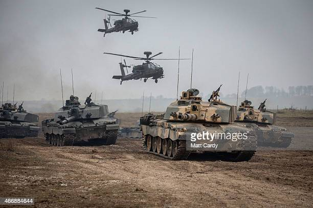 Apache helicopters hover above a column of Army vehicles including Challenger 2 Warrior and FV 432's belonging to 1 Yorks and Kings Royal Hussars as...