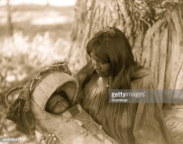 Apache woman at base of tree holding infant in cradleboard in her lap
