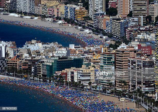 Apartament blocks are pictured along the waterfront behind beach goers in Benidorm near Alicante on August 9 2016 / AFP / JOSE JORDAN