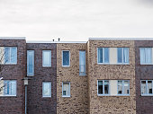 Architectural Exterior Detail of Residential Apartment Building with Small Windows and Brown Brick Facade with Cloudy Overcast Sky in Background