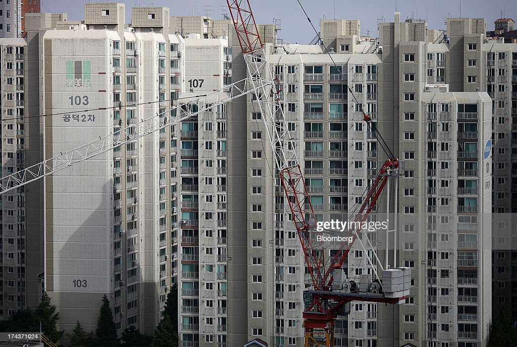 Apartment buildings stand behind construction cranes in the district of Mapo in Seoul, South Korea, on Wednesday, July 24, 2013. South Koreas economy grew the most in more than two years, on stronger government spending and private consumption even as a slowdown in China clouds the outlook. Photographer: Woohae Cho/Bloomberg via Getty Images