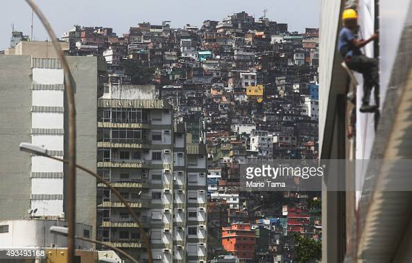 Apartment buildings stand next to houses in the Rocinha 'favela' community on October 20 2015 in Rio de Janeiro Brazil Residential real estate prices...