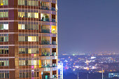 Apartment windows in the night time.  Big city living in highrise urban environment.  Real estate concept.