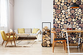 Modern bright apartment with beige sofa, yellow armchair, table and wooden decor