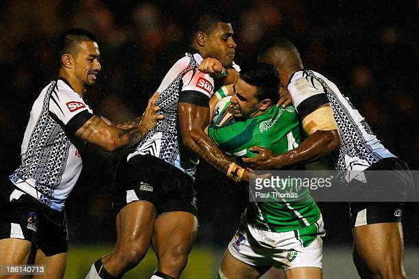 Apirana Pewhairangi of Ireland is tackled by Fiji's Kevin Naiqama and Waisale Ligani Naiqama during the Rugby League World Cup Group A match between...
