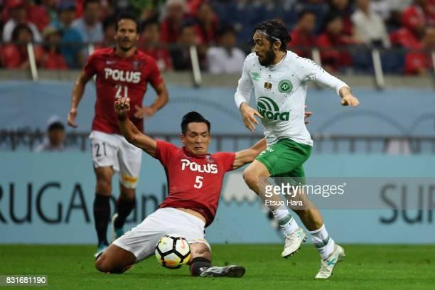 Apodi of Chapecoense is tackled by Tomoaki Makino of Urawa Red Diamonds during the Suruga Bank Championship match between Urawa Red Diamonds and...
