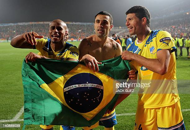 Apoel's Brazilian players William Boaventura Marcelo Oliveira and Kaka hold their national flag as they celebrate their team's win against Lyon's...