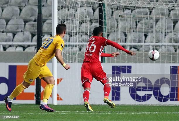 Apoel's forward Pieros Sotiriou scores past Olympiacos' defender Bruno Viana during the Europa League Group B football match between Cyprus' APOEL FC...
