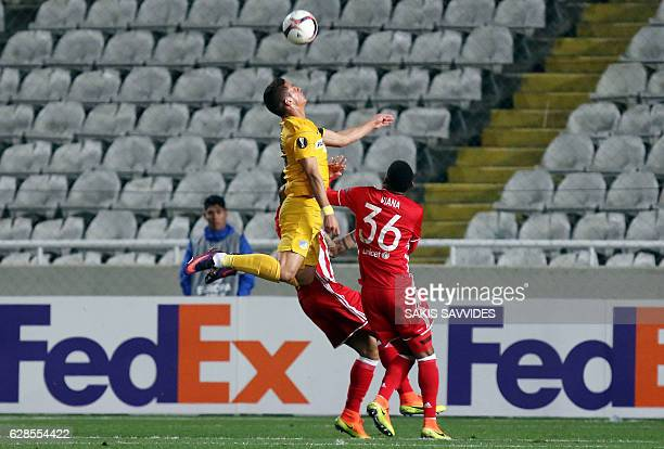 Apoel's forward Pieros Sotiriou wins the header ahead of Olympiacos' defender Bruno Viana during the Europa League Group B football match between...