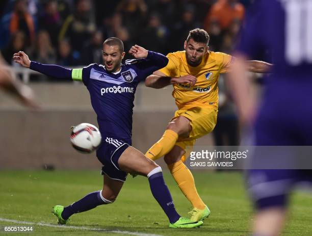 Apoel's Spanish forward David Barral is tackled by Anderlecht's Algerian midfielder Sofiane Hanni during the Europa League round of 16 football match...