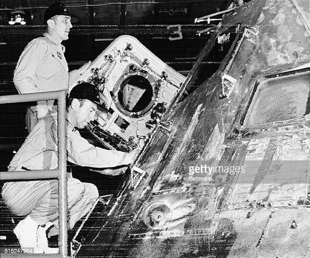 Apollo astronauts John Swigert and James Lovell examine their Apollo 13 command module on the hanger deck of the USS Iwo Jima on 4/17 NASA officials...