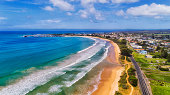 Beatiful sand beach of Apollo bay town on Great Ocean road towards enclosed harbour, marina and town houses waterfront from above.