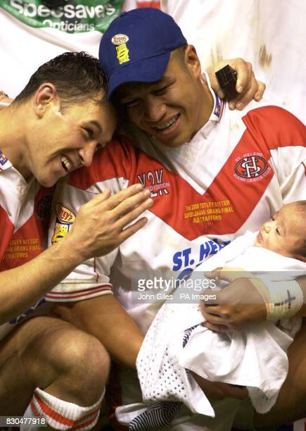 Apollo Perillini of St Helens holding his baby with Sean Hoppe after their victory in the Super League Grand Final against Wigan at Old Trafford