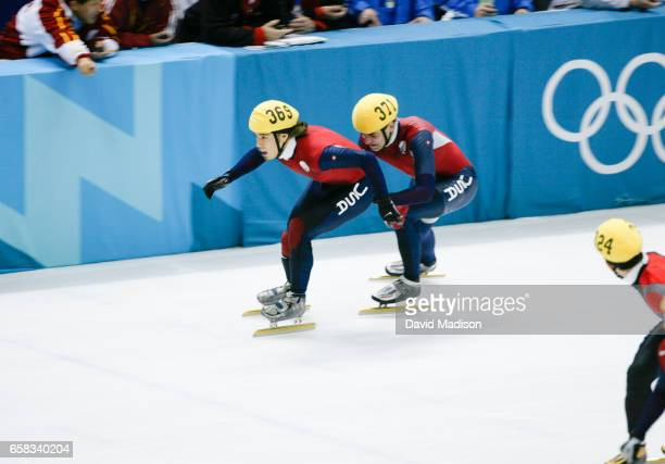Apolo Ohno of the USA gets a push from teammate Daniel Weinstein during the Men's 5000 meter Relay of the Short Track speed skating competition at...
