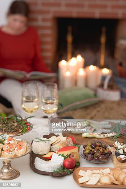 Appetisers on table, woman in background reading a book