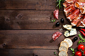 Top view of a rustic wood table with delicatessen like prosciutto, salami, black olives, crostini, blue cheese and some herbs at the right border leaving a useful copy space.  DSRL studio photo taken