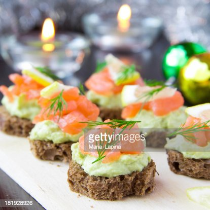 Appetizer canapes of bread with avocado, red fish salmon, lemon : Stock Photo