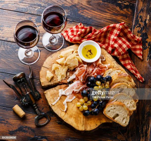 Appetizer ham and cheese plate with wine on wooden table background
