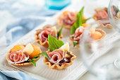 Appetizers with prosciuto crudo, melon balls, figs, parmesan cheese and basil. Shallow dof.