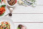 Appetizing meat side dishes frame flat lay. Top view on white wooden table with warm salads. Restaurant menu, buffet, banquet, party concept