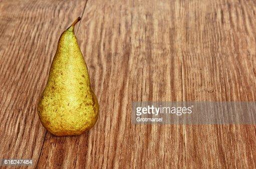Appetizing sweet pear on grunge wooden background taken closeup. : Foto de stock
