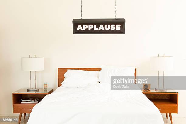 'Applause' sign hanging over bed.