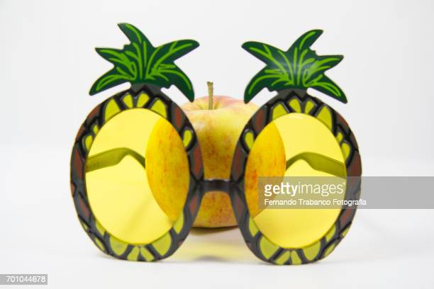 Apple behind a pineapple-shaped glasses
