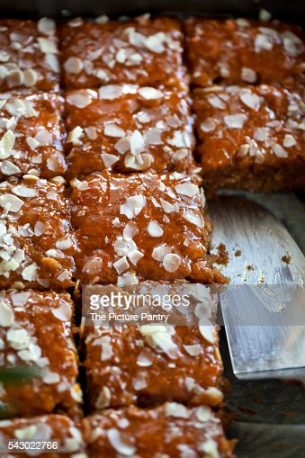 Apple cake topped with apricot jam and slivered almonds