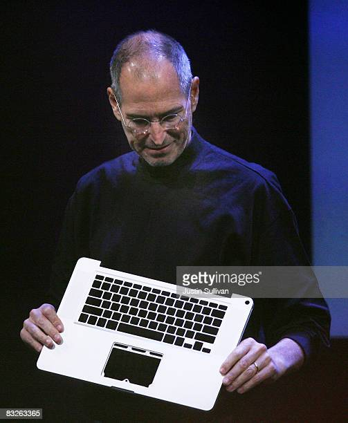 Apple CEO Steve Jobs holds up an aluminum unibody used in the MacBook Pro during a 'town hall' style event at Apple Headquarters October 14 2008 in...