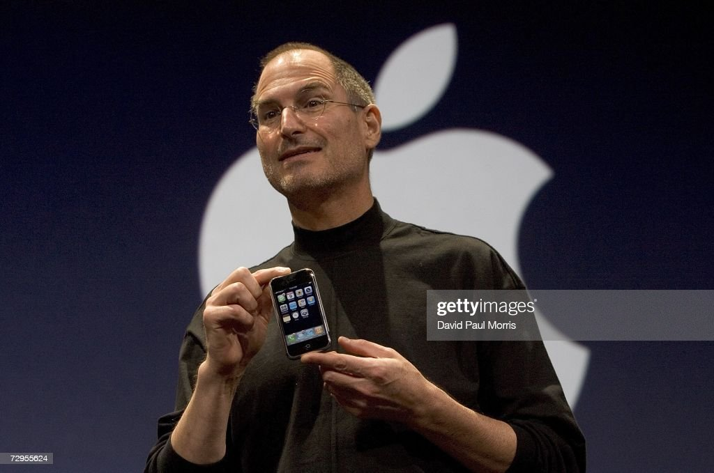 Apple CEO Steve Jobs holds up the new iPhone that was introduced at Macworld on January 9, 2007 in San Francisco, California. The new iPhone will combine a mobile phone, a widescreen iPod with touch controls and a internet communications device with the ability to use email, web browsing, maps and searching. The iPhone will start shipping in the US in June 2007.