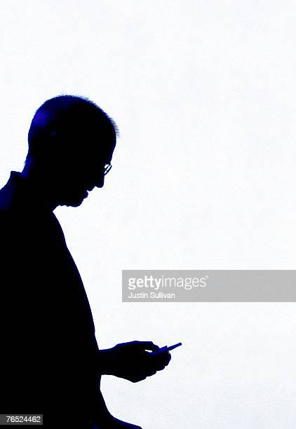 Apple CEO Steve Jobs is silhouetted by a video screen as he shows a new iPod video during an Apple Special event September 5 2007 in San Francisco...