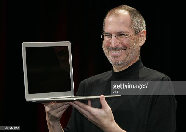 Apple CEO Steve Jobs smiles as he shows off the new Macbook Air an ultra portable laptop during his keynote speech at the MacWorld Conference Expo in...