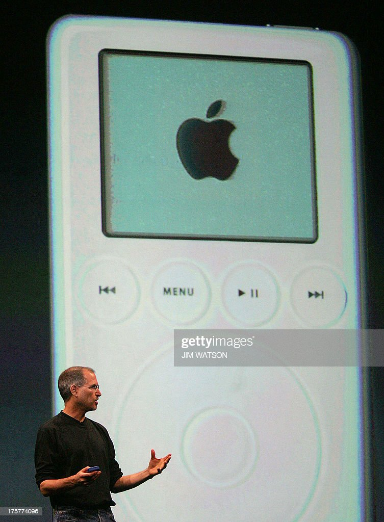 Apple CEO Steve Jobs speaks in front of a picture of the iPod during Apple's announcement of the release of Apple 'iTunes' Music Store in the UK...