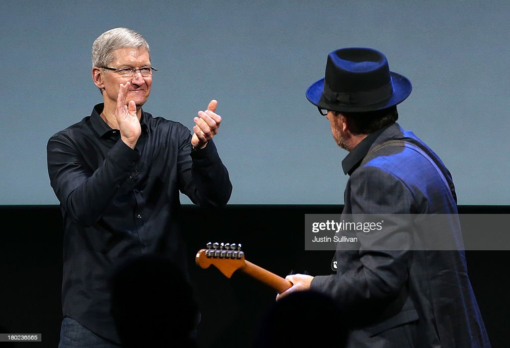 Apple CEO Tim Cook (L) applauds as musician Elvis Costello (R) walks on stage during an Apple product announcement at the Apple campus on September 10, 2013 in Cupertino, California. The company launched the new iPhone 5C model that will run iOS 7 is made from hard-coated polycarbonate and comes in various colors and the iPhone 5S that features fingerprint recognition security.