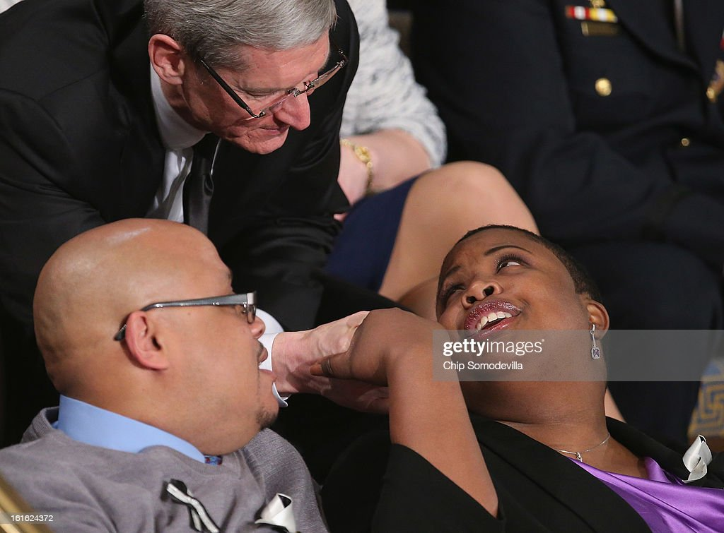 Apple CEO Tim Cook (top) greets Cleopatra Cowley-Pendleton (R) and Nathaniel A. Pendleton Sr. of Chicago, Illinois before U.S. President Barack Obama's State of the Union speech at the U.S. Capitol February 13, 2013 in Washington, DC. The Pendleton's daughter, Hadiya Pendleton, was murdered on January 29, 2013, when she was shot and killed in Harsh Park on ChicagoÕs South Side.