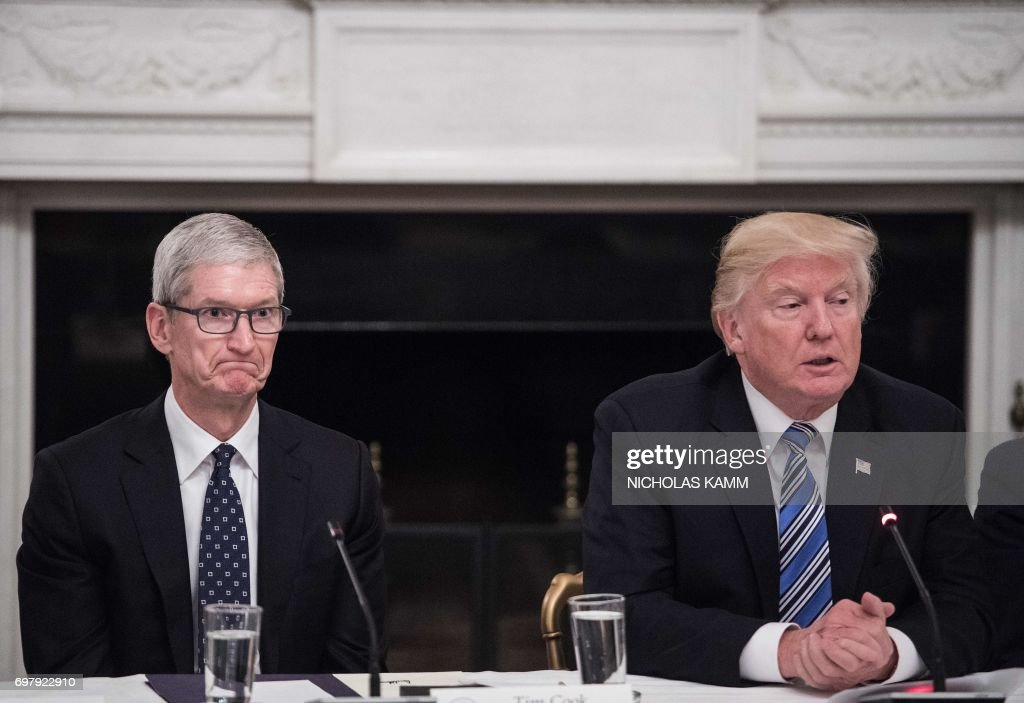 Apple CEO Tim Cook (L) listens to US President Donald Trump during an American Technology Council roundtable at the White House in Washington, DC, on June 19, 2017. /