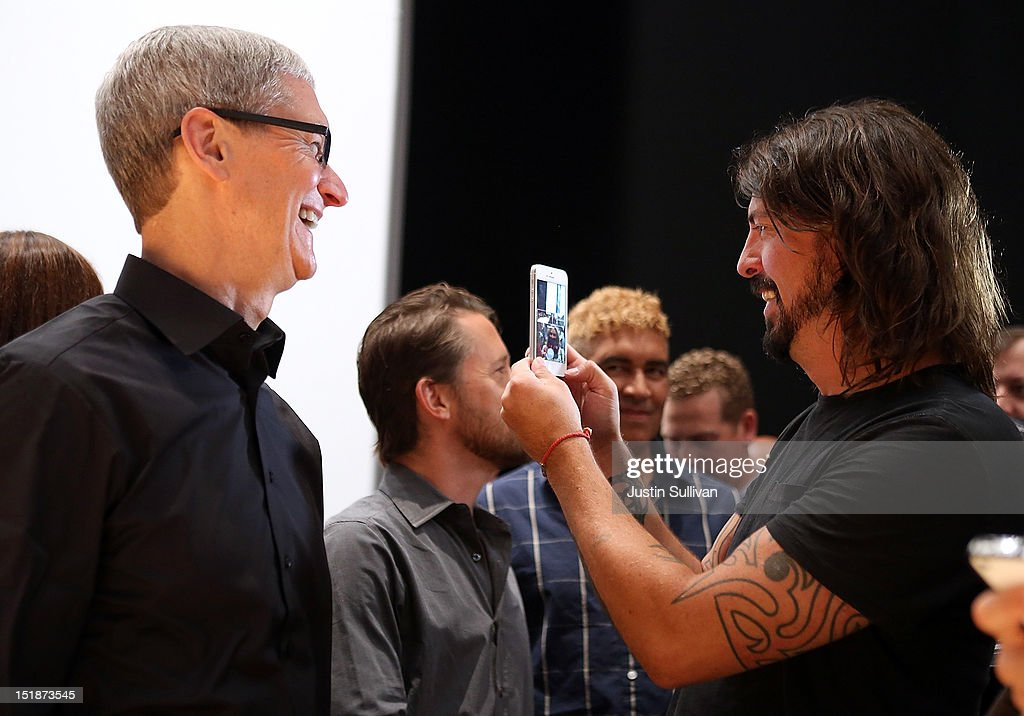 Apple CEO Tim Cook (L) looks on as <a gi-track='captionPersonalityLinkClicked' href=/galleries/search?phrase=Dave+Grohl&family=editorial&specificpeople=202539 ng-click='$event.stopPropagation()'>Dave Grohl</a> of the Foo Fighters looks at the new iPhone 5 during an Apple special event at the Yerba Buena Center for the Arts on September 12, 2012 in San Francisco, California. Apple announced the iPhone 5, the latest version of the popular smart phone.