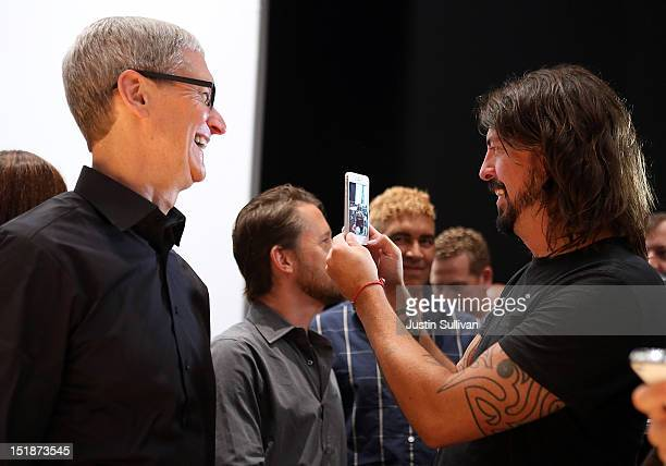 Apple CEO Tim Cook looks on as Dave Grohl of the Foo Fighters looks at the new iPhone 5 during an Apple special event at the Yerba Buena Center for...