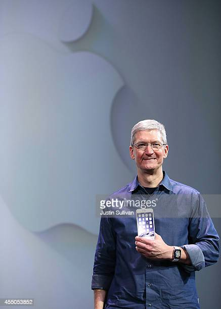 Apple CEO Tim Cook models the new iPhone 6 and the Apple Watch during an Apple special event at the Flint Center for the Performing Arts on September...