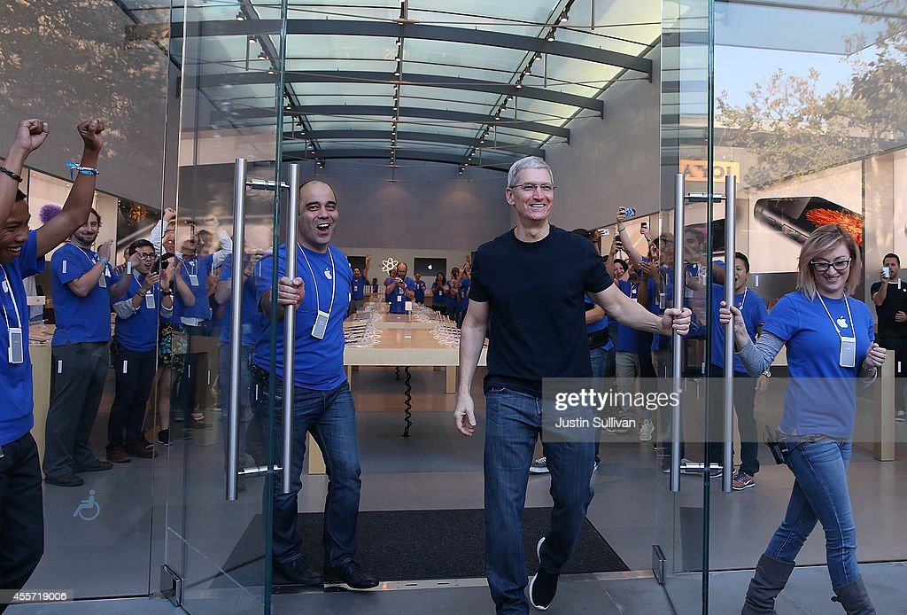 Apple CEO Tim Cook (R) opens the door to an Apple Store to begin sales of the new iPhone 6 on September 19, 2014 in Palo Alto, California. Hundreds of people lined up to purchase the new iPhone 6 and iPhone 6 Plus that went on sale today.