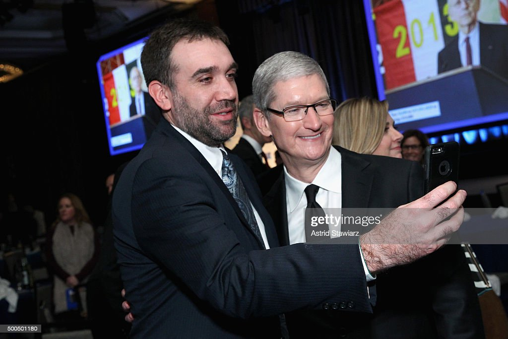 Apple CEO Tim Cook poses with a guest as Robert F. Kennedy Human Rights hosts The 2015 Ripple Of Hope Awards honoring Congressman John Lewis, Apple CEO Tim Cook, Evercore Co-founder Roger Altman, and UNESCO Ambassador Marianna Vardinoyannis at New York Hilton on December 8, 2015 in New York City.